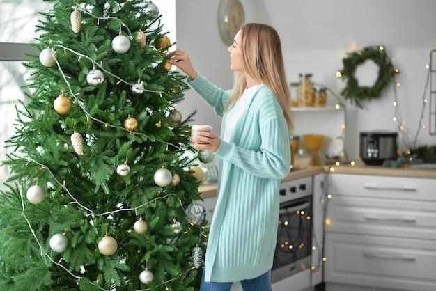Mulher jovem e bonita bebendo chocolate quente em casa na véspera de natal
