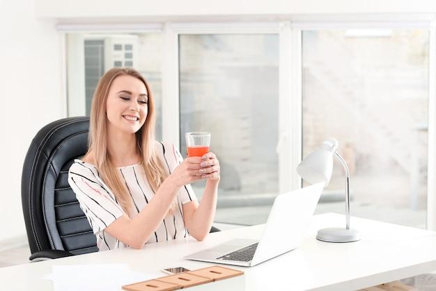 Mulher jovem e bonita bebendo suco de frutas cítricas no escritório