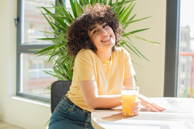 Mulher jovem e bonita bebendo suco