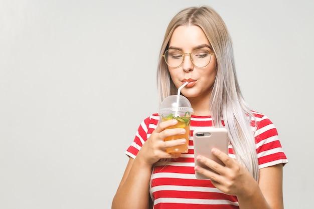 Mulher jovem e bonita bebendo um suco de desintoxicação caseiro, enviando mensagens de texto em seu telefone enquanto isolado sobre o branco. usando o telefone.