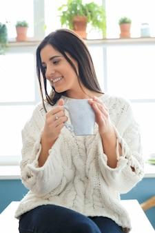 Mulher jovem e bonita bebendo uma bebida quente na cozinha