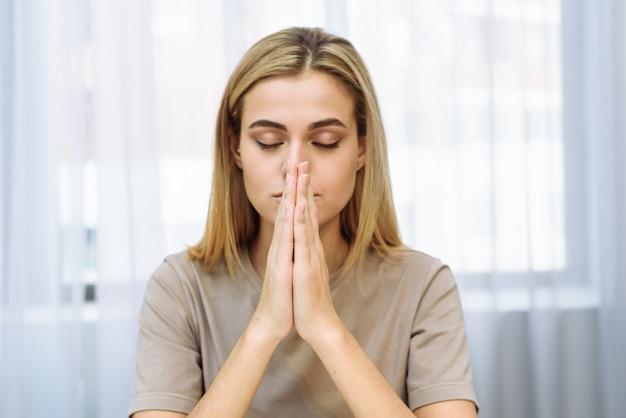 Mulher jovem e bonita bonita cruzou as mãos em oração. uma mulher pede ajuda a deus.