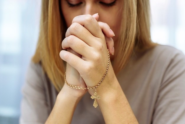 Mulher jovem e bonita bonita cruzou as mãos em oração.