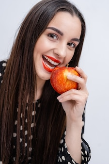 Mulher jovem e bonita bonita, modelo, menina com lábios vermelhos. menina comendo uma maçã, sorrindo. fechar-se