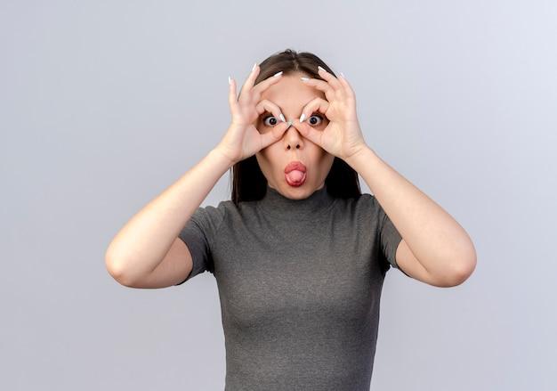 Mulher jovem e bonita brincalhona fazendo gesto de olhar usando as mãos como binóculos e mostrando a língua isolada no fundo branco