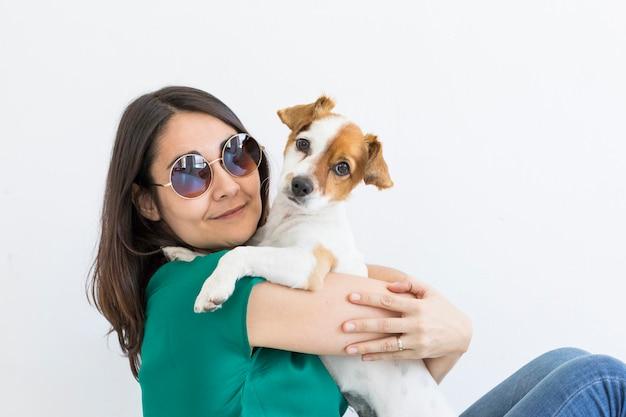 Mulher jovem e bonita brincando com seu cachorrinho fofo em casa.