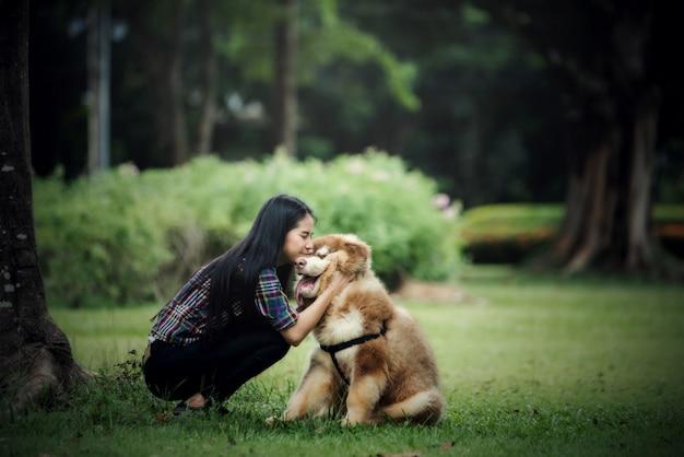 Mulher jovem e bonita brincando com seu cachorro pequeno em um parque ao ar livre. retrato do estilo de vida.