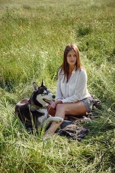 Mulher jovem e bonita brincando com um cachorro husky engraçado ao ar livre no parque