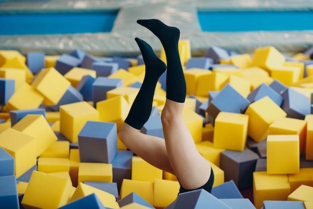 Mulher jovem e bonita brincando na piscina seca com cubos. pernas para cima.