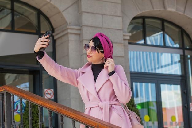 Mulher jovem e bonita caminhando com um telefone