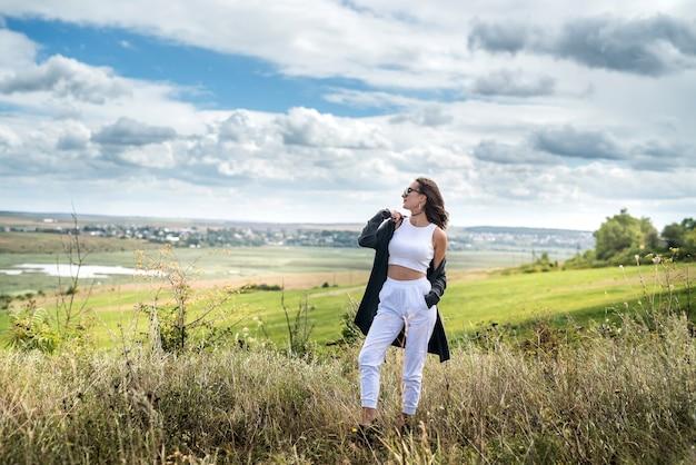 Mulher jovem e bonita caminhando em um campo verde rural, horário de verão