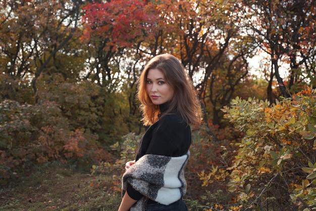 Mulher jovem e bonita caminhando na floresta de outono. clima quente e ensolarado