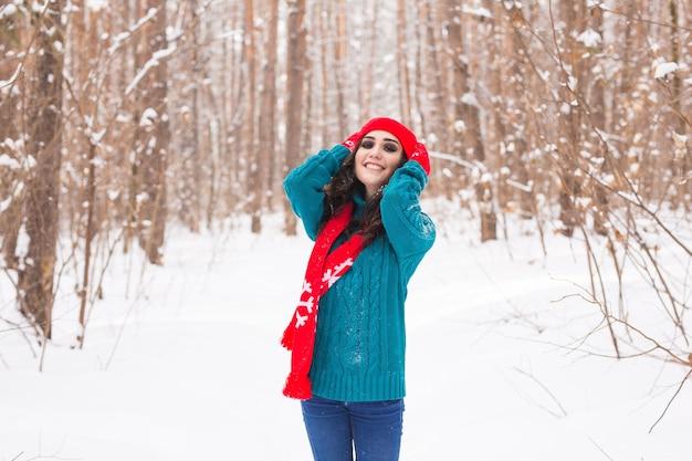 Mulher jovem e bonita caminhando na natureza de inverno nevado