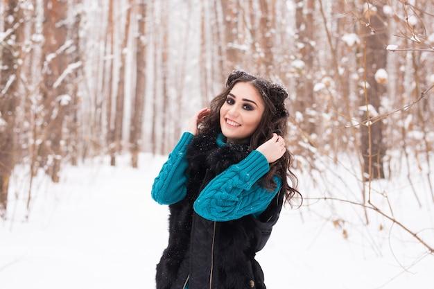 Mulher jovem e bonita caminhando na natureza de neve de inverno