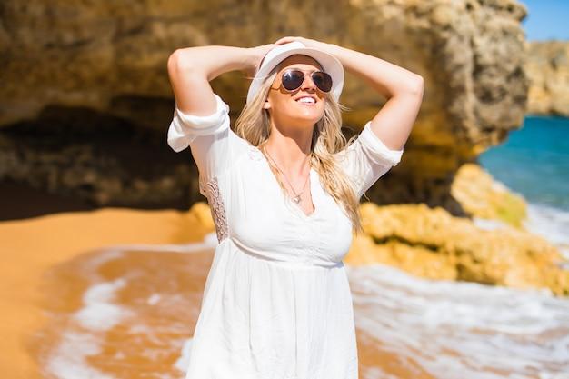 Mulher jovem e bonita caminhando na praia no verão