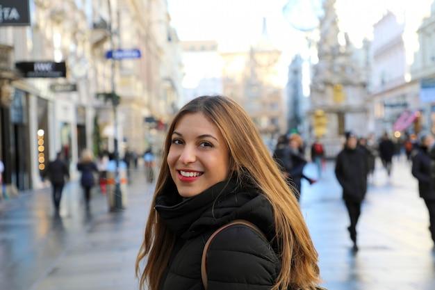 Mulher jovem e bonita caminhando por viena com a famosa coluna