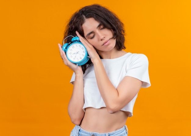 Mulher jovem e bonita cansada segurando o despertador e colocando a cabeça nele na parede laranja isolada com espaço de cópia