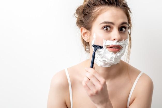 Mulher jovem e bonita caucasiana, barbeando o rosto com uma navalha. mulher bonita com espuma de barbear no rosto