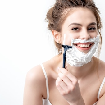 Mulher jovem e bonita caucasiana, barbeando o rosto por navalha em fundo branco. mulher bonita com espuma de barbear no rosto