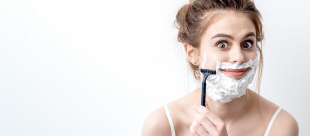 Mulher jovem e bonita caucasiana, barbeando o rosto por navalha na parede branca. mulher bonita com espuma de barbear no rosto