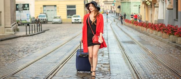 Mulher jovem e bonita caucasiana caminhando com uma mala em uma pista de bonde molhada na cidade europeia