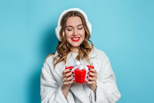 Mulher jovem e bonita caucasiana com batom vermelho, vestindo um casaco branco de pele falsa e orelhas de pele
