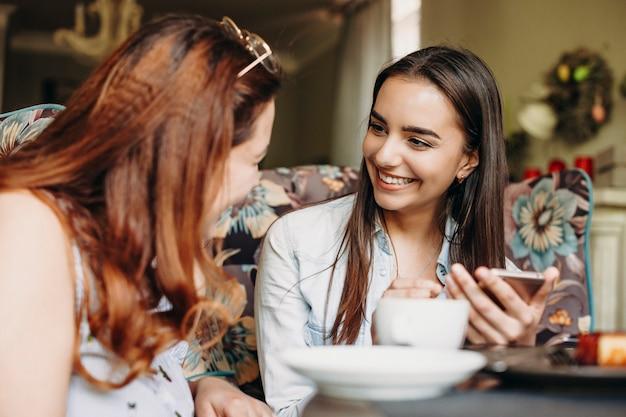Mulher jovem e bonita caucasiana com cabelo comprido escuro, olhando para sua amiga sorrindo, segurando um smartphone enquanto está sentado no restaurante.