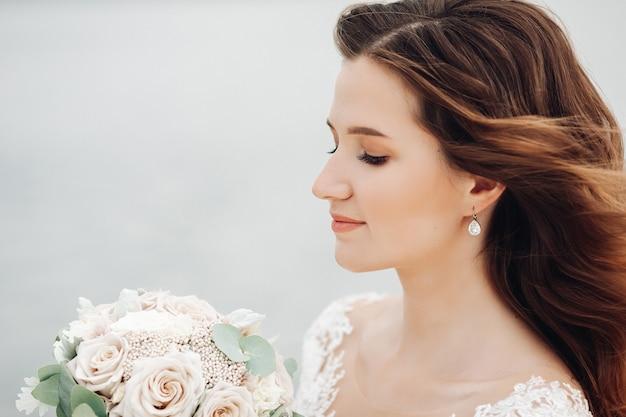 Mulher jovem e bonita caucasiana com cabelos ondulados segurando um buquê de noiva nas mãos e sorrindo