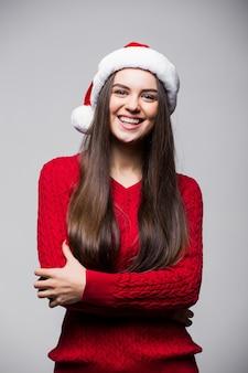 Mulher jovem e bonita caucasiana com chapéu de papai noel e luvas posando sorrindo contra uma parede cinza claro. conceito de natal e ano novo. copie o espaço disponível.