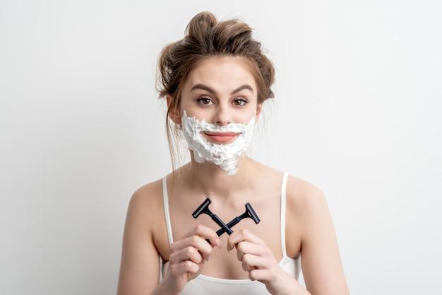 Mulher jovem e bonita caucasiana com espuma de barbear no rosto e duas navalhas nas mãos no fundo branco