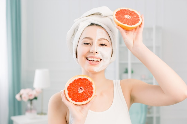 Mulher jovem e bonita caucasiana com máscara de limpeza branca na metade do rosto e toranja halfs no espaço claro. cosméticos naturais, skincare, bem-estar, tratamento facial, conceito de cosmetologia.
