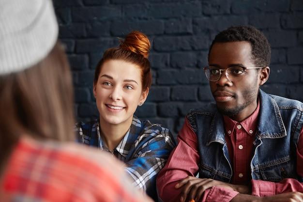 Mulher jovem e bonita caucasiana com sorriso alegre e um homem africano moderno usando óculos