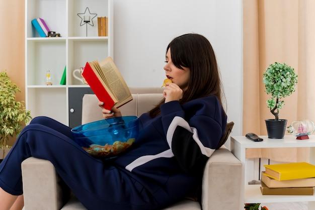Mulher jovem e bonita caucasiana concentrada sentada em uma poltrona em uma sala projetada segurando uma tigela de batatas fritas nas pernas, comendo batata frita e lendo um livro