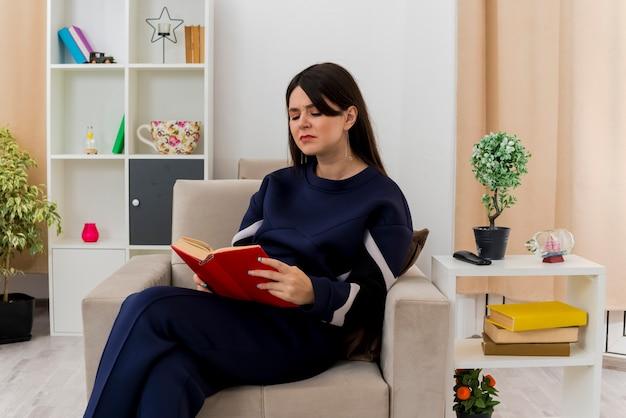 Mulher jovem e bonita caucasiana descontente sentada com as pernas cruzadas na poltrona em uma sala projetada segurando e lendo um livro
