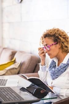 Mulher jovem e bonita caucasiana em casa, trabalho ou estudo com dois laptops pessoais na mesa - conceito de pessoas estudando com mais de 40 anos de idade - mulher de negócios livre do escritório