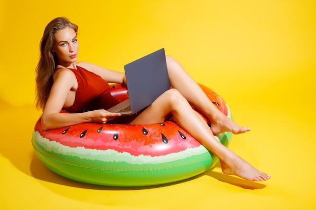 Mulher jovem e bonita caucasiana em maiô isolado em fundo amarelo. conceito de resto de férias de verão de pessoas. sente-se no anel inflável de natação, trabalhe no computador laptop.