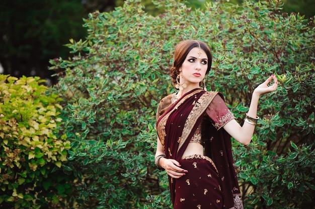 Mulher jovem e bonita caucasiana em roupas indianas tradicionais sari com maquiagem de noiva e jóias e tatuagem de henna nas mãos.
