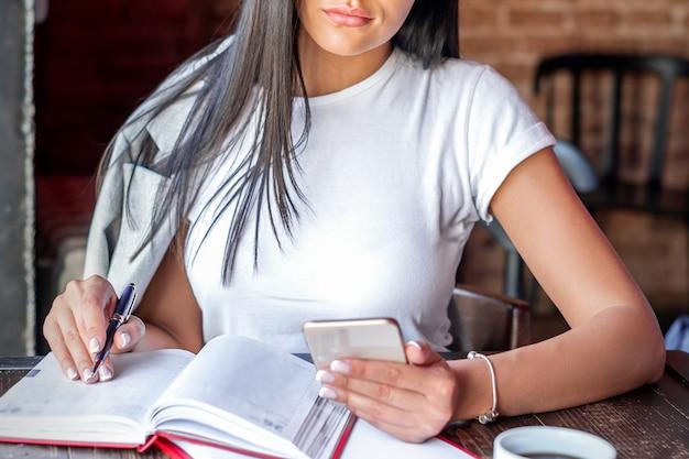 Mulher jovem e bonita caucasiana escreve notas no bloco de notas segurando o smartphone na mão usando óculos no café