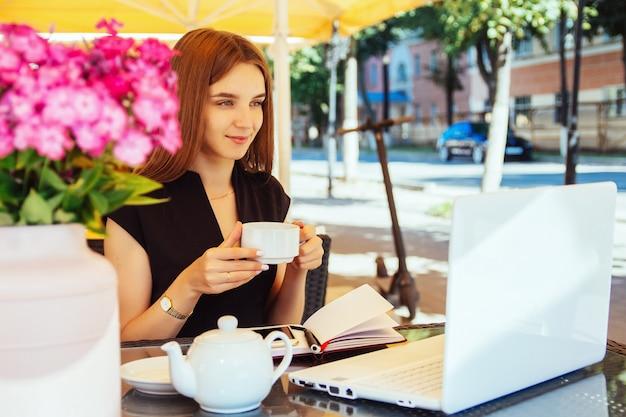 Mulher jovem e bonita caucasiana está sentada à mesa com um laptop em um café, bebendo chá e sorrindo. o conceito de trabalho remoto, freelancer e ensino à distância online