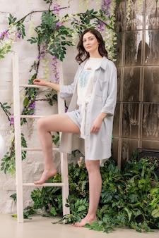 Mulher jovem e bonita caucasiana posando junto à escada para toalhas no banheiro.