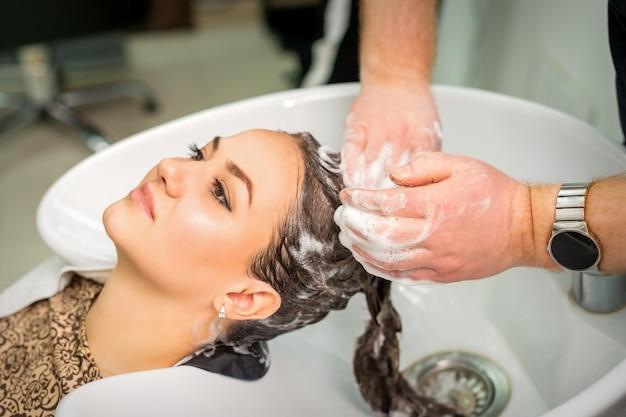 Mulher jovem e bonita caucasiana recebendo lavagem de cabelo por mãos masculinas de cabeleireiro em salão de cabeleireiro