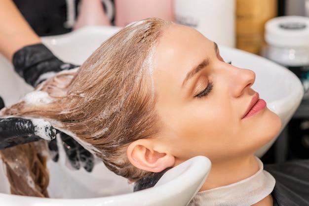 Mulher jovem e bonita caucasiana recebendo lavar o cabelo em um salão de cabeleireiro