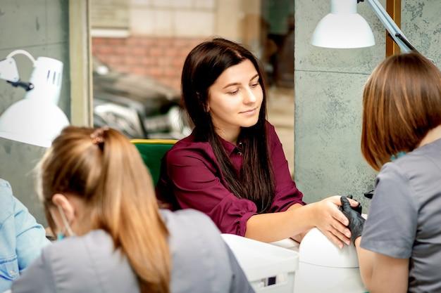 Mulher jovem e bonita caucasiana recebendo tratamento de unhas, sentada em um salão de beleza