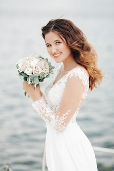 Mulher jovem e bonita caucasiana segurando um buquê de noiva nas mãos e sorrindo