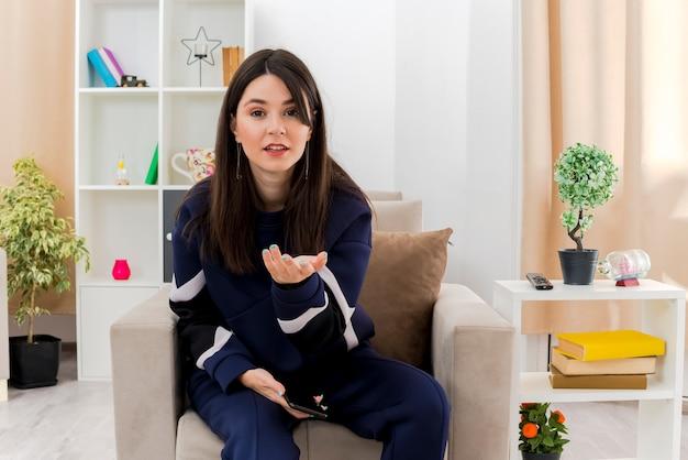 Mulher jovem e bonita caucasiana sem noção, sentada na poltrona na sala projetada, segurando um telefone celular, olhando e mostrando a mão vazia