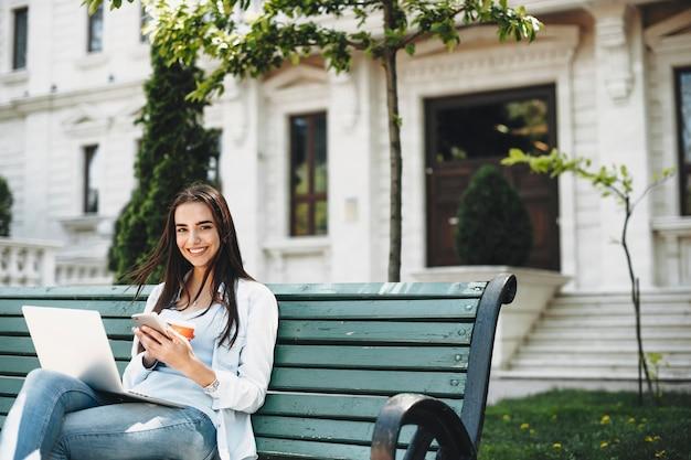 Mulher jovem e bonita caucasiana sentada em um banco usando um smartphone com um laptop nas pernas, olhando para a câmera sorrindo contra um edifício moderno.