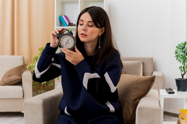 Mulher jovem e bonita caucasiana sentada em uma poltrona em uma sala projetada segurando e olhando para o despertador