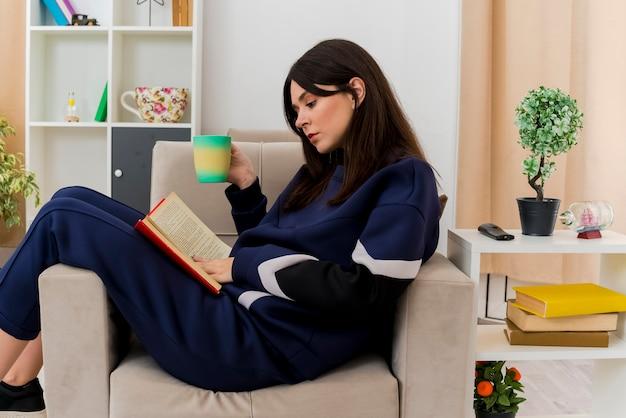 Mulher jovem e bonita caucasiana sentada em uma poltrona em uma sala projetada segurando uma xícara com um livro nas pernas, tocando e lendo um livro