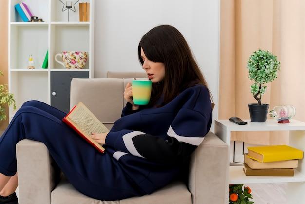 Mulher jovem e bonita caucasiana sentada na poltrona na sala projetada segurando um copo com um livro nas pernas, tocando e lendo o livro e se preparando para beber café