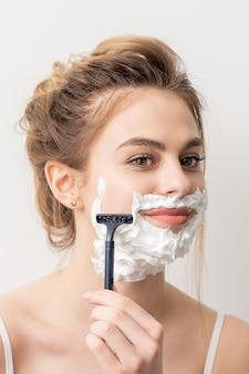 Mulher jovem e bonita caucasiana sorridente, barbeando o rosto com navalha no fundo branco